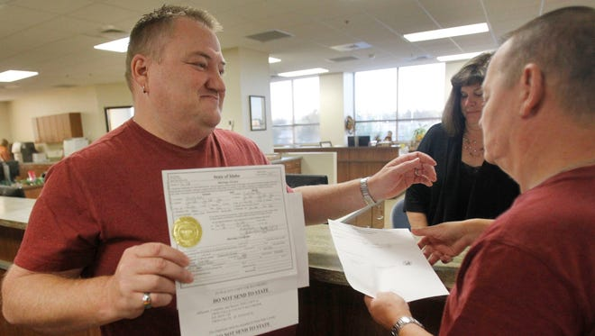 Don Moline holds up a marriage license as he prepares to embrace his partner, Clint Newlan, the morning after a federal appeals court struck down Idaho's ban on same-sex marriage.