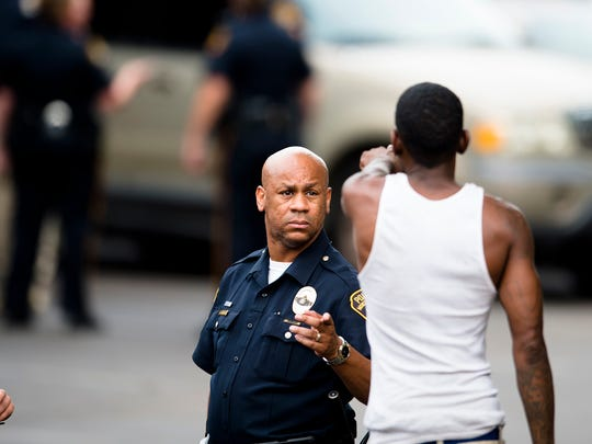 A pedestrian talks to a Montgomery Police Officer as