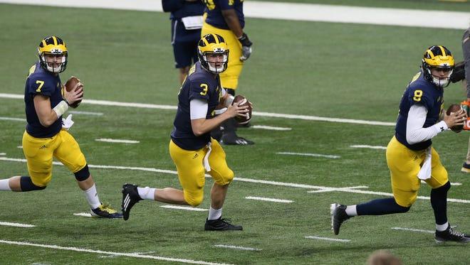 Michigan quarterbacks Shane Morris (7), Wilton Speight (3) and John O'Korn (8) go through drills at Ford Field in Detroit on March 26, 2016.