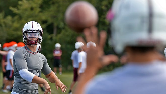 Dowling Catholic quarterback Ryan Boyle, left, warms up during football practice this past Tuesday.