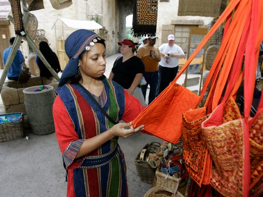 Odeymis Marcano, an employee at the Holy Land Experience, checks merchandise at one of the gift shops.