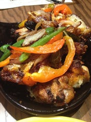 Delicio's wings are marinated in a vinaigrette and roasted in a coal-fired oven,  and then served either with fajita vegetable mix or a sweet red chili.