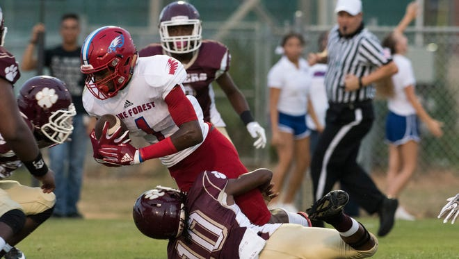 Pine Forest High School's Martin Emerson,(No. 1) gets wrapped up by Pensacola High Shcool's Deaaron Finklea,(No. 10) during the season opener Friday night.