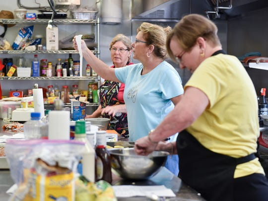 Judy Friede, foreground, stirs ingredients in a bowl as Annette Carter checks a recipe with Wendy Womble as they prepare dishes for the Second Sunday meal.