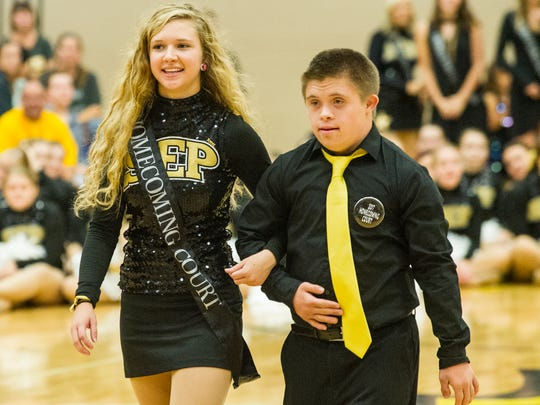 Kennedy Varisco and Tyler Kaut walk to their seats after their introduction at the 2017 Southeast Polk High School homecoming coronation ceremony.