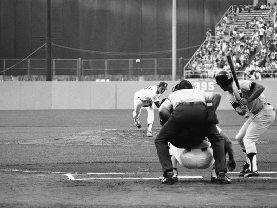 Los Angeles Dodgers pitcher Burt Hooton watches the flight of his ball as he tosses the first pitch in game two of the World Series Wednesday, Oct. 11, 1978 in Los Angeles. At bat for the Yankees is Roy White. Catcher is Dodgers Steve Garvey,  umpire is Bill Haller of the American League. The first pitch was a ball. (AP Photo)