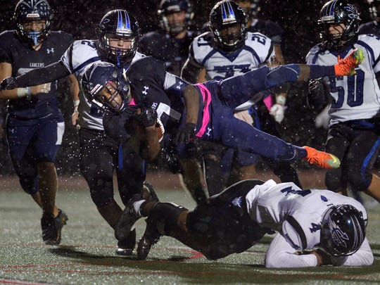 Eastridge's Rayshauid Smith is upended by Brockport's Raphael Odey near the goal line during a Section V Class A quarterfinal game at Eastridge High School on Oct. 21, 2016.
