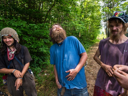 David Danforth of Buffalo, New York, who goes by the name Thankful, center, enjoys a laugh with Edgar Plett of Planet Earth, left, and Beaker, right,as they attend the Rainbow Family National Gathering in the Green Mountain National Forest in Mt. Tabor on Tuesday, June 28, 2016.
