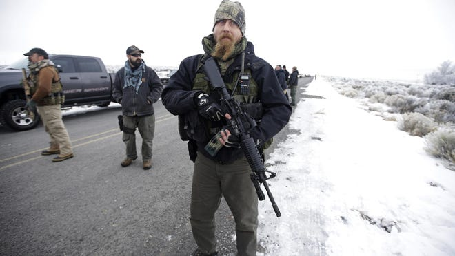 "FILE - In this Jan. 9, 2016 file photo a man stands guard after members of the ""3% of Idaho"" group and several other organizations arrive at the Malheur National Wildlife Refuge near Burns, Ore. When armed protesters took over a remote wildlife refuge in eastern Oregon four years ago to oppose federal control of public lands, U.S. agents negotiated with the conservative occupiers for weeks while some state leaders begged for stronger action. This month, federal officers sent to Portland to quell chaotic protests against racial injustice took swift and, some say, harsh action: launching tear gas, firing less-lethal ammunition and helping arrest more than 40 people in the first two weeks."