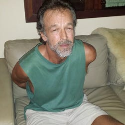 In this photo released by Rio Grande do Norte State Security secretary, American sect leader Victor Arden Barnard sits in a police station after being detained at Pipa beach, in the Northeastern state of Rio Grande do Norte, Brazil, Friday, Feb. 27, 2015.