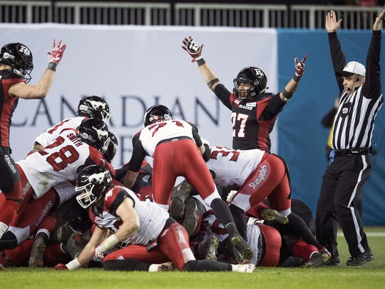 Ottawa Redblacks quarterback Henry Burris (obscured) scores a touchdown as wide receiver Greg Ellingson (82) and running back Kienan Lafrance (27) look on during fourth-quarter CFL Grey Cup football game action against the Calgary Stampeders, Sunday, Nov. 27, 2016, in Toronto. (Frank Gunn/The Canadian Press via AP)