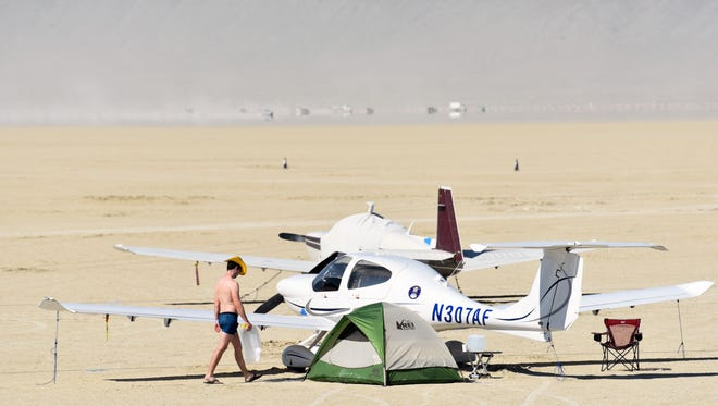 Pilot Scott Bruce, wearing underwear and a gold cowboy hat, walks to his airplane at Black Rock City airport.