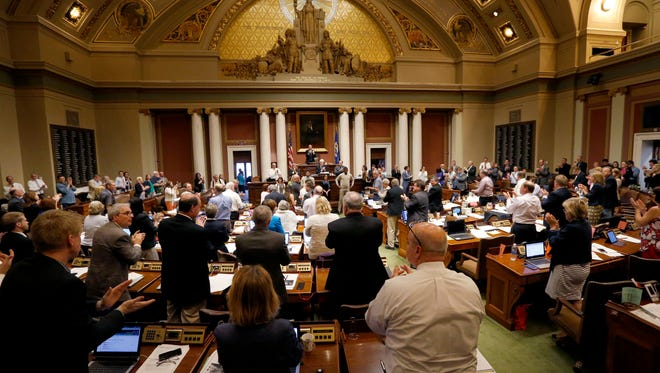 Minnesota House members applaud during the final day of the 2016 session.