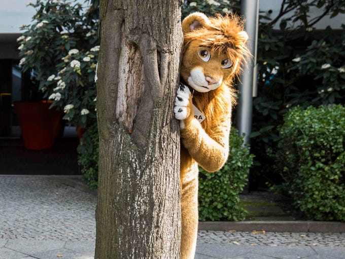 A delegate dressed in a furry Lion costume peeks out