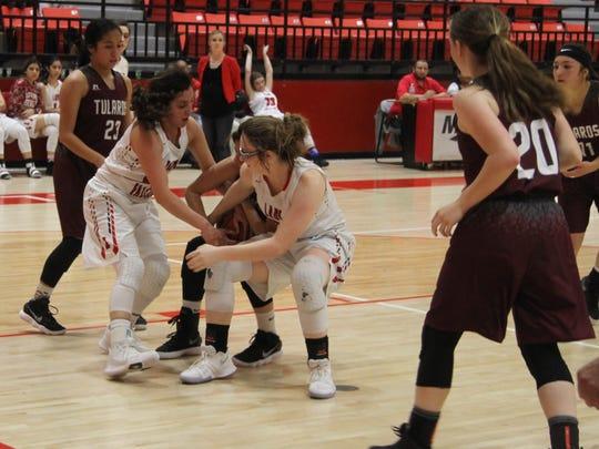 Senior Alyssa Carrasco and junior Jacelyn Johnson fight for a offense rebound against Tularosa Thursday, Feb. 1, 2018.