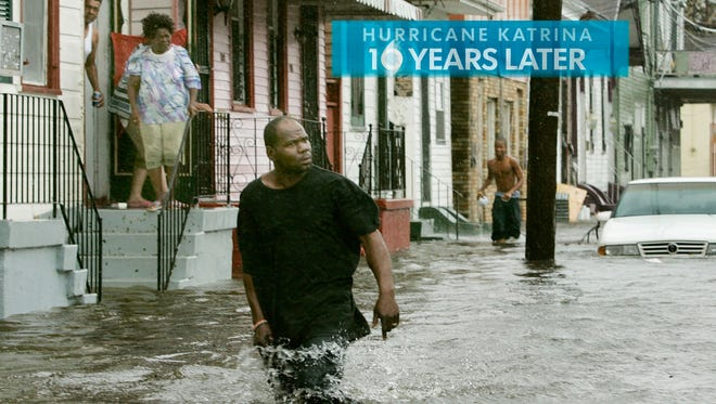 People come out of thier homes to a flooded street after Hurricane Katrina hit the area with heavy wind and rain August 29, 2005 in New Orleans.