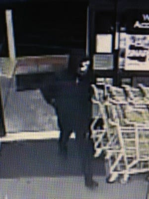 A surveillance photo shows the masked man who robbed a dollar store on Tuesday night.