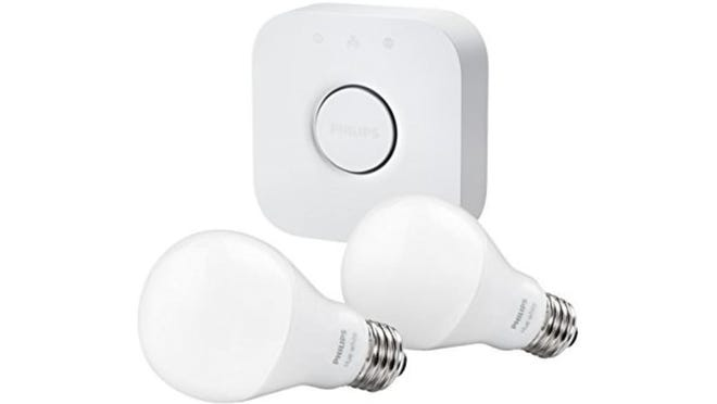 """Two Philips Hue lightbulbs with the """"Bridge"""" unit that connects to the router and controls the system"""