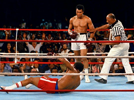 Referee Zack Clayton, right, steps in after Muhammad Ali knocks out George Foreman in the eighth round.