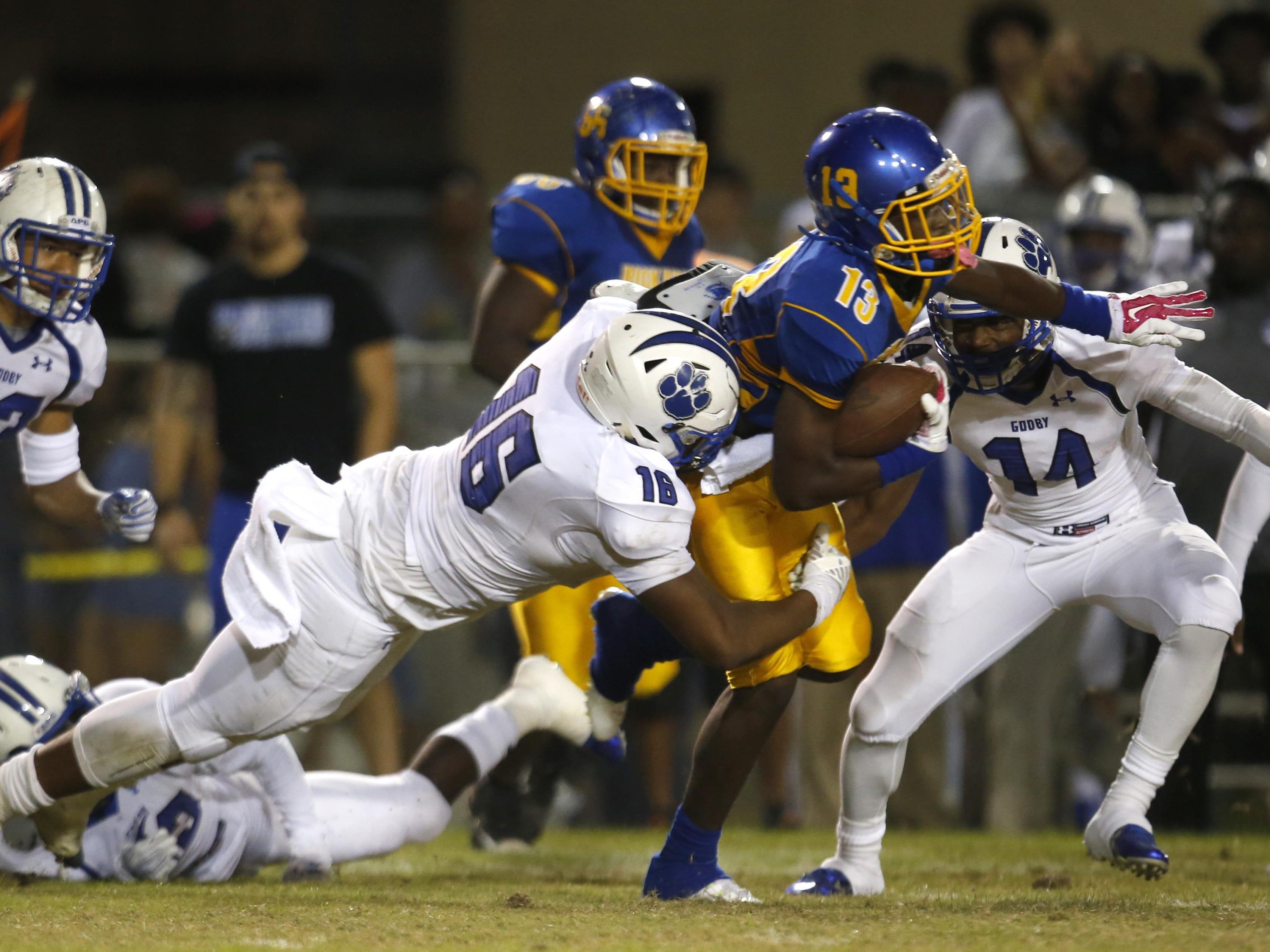 Godby's Antwan Owens tackles Rickards' Chad Hunter after a reception during their game at Cox Stadium on Friday.