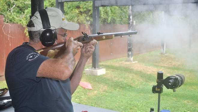 A puff of smoke emerges from Bob King's Hawken musket during a competition Saturday at the Newport Rifle Club.