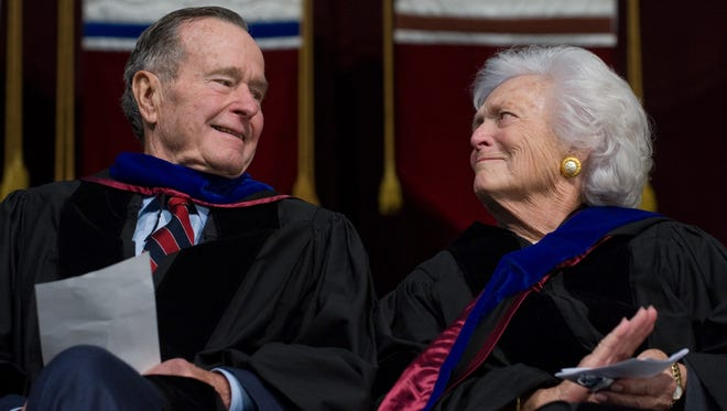 President George H.W. Bush and Barbara Bush listen Dec. 12, 2008, as their son, then-President George W. Bush, delivers the commencement address during the Texas A&M University graduation ceremony in College Station, Texas.