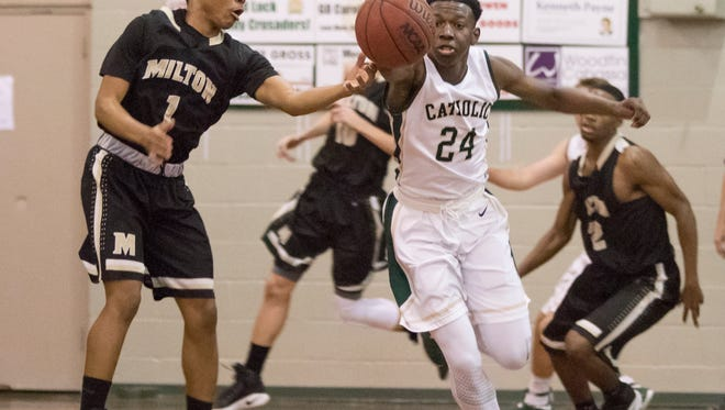 DJ Mckenzie (24) steals a pass to Chris Carter (1) during the Milton vs. Catholic basketball game at Catholic High School in Pensacola on Tuesday, December 27, 2016.