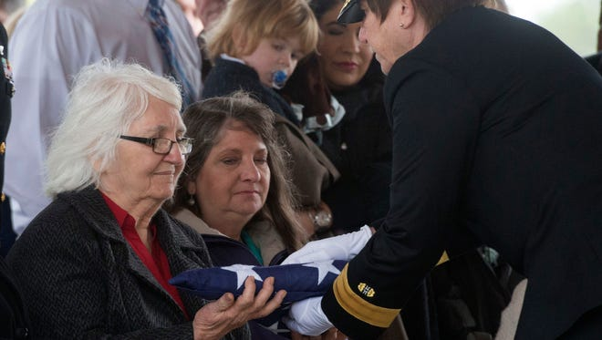 Rear Adm. Carol Lynch, right, presents, Jean Bodiford, the flag draped over the casket family member,  Walter Henry Sollie, at the conclusion of the War War II veteran's funeral Friday morning. The remains of Sollie, a sailor serving onboard the USS Oklahoma during the Japanese attack on Pearl Harbor, was recently identified by the using DNA.