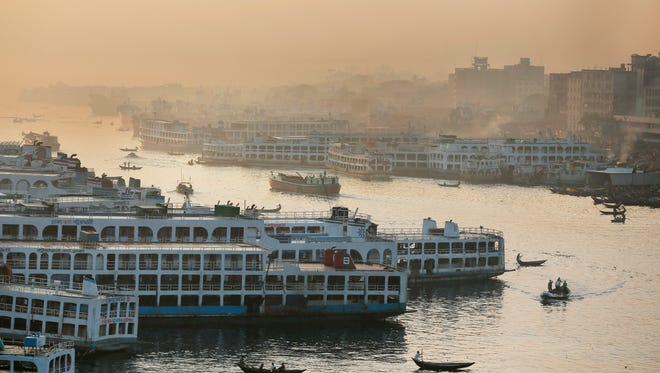 Ferries are moored to a dock as small boats maneuver on the Buriganga Rver in Dhaka, Bangladesh, on Dec. 10, 2015.