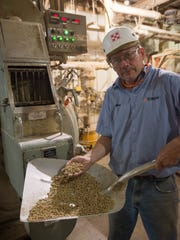 Mike Bergan stands in front of the pelletizer at the Purina Animal Nutrition feed manufacturing plant in Mason City, Iowa. A new motor and dies will increase the plant's capacity to manufacture pelleted livestock feeds by 25 percent.