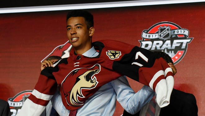 Pierre-Olivier Joseph puts on a team jersey after being selected as the number twenty-three overall pick to the Arizona Coyotes in the first round of the 2017 NHL Draft at the United Center.