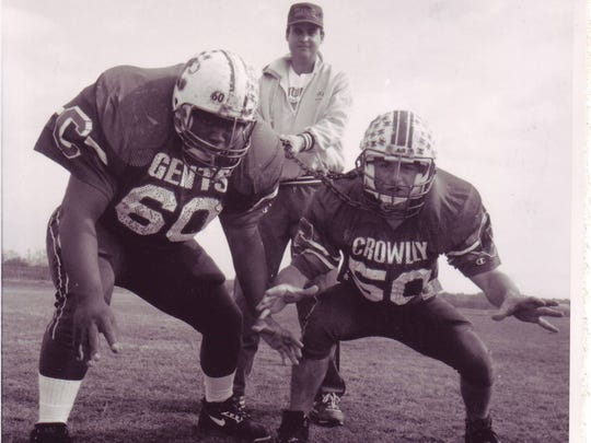 Crowley High coach Kevin Magee tried his best to hold back the Gents' fearsome defensive duo of Terrell Malbrough (60) and Brad Pommier (50) prior to the 1992 season.