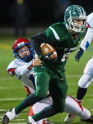 St. Johnsbury's Jasper Rankin, right, breaks away from Hartford's Tyler Hailton in the Division 1 high school football state championship in Rutland on Saturday, November 11, 2017.