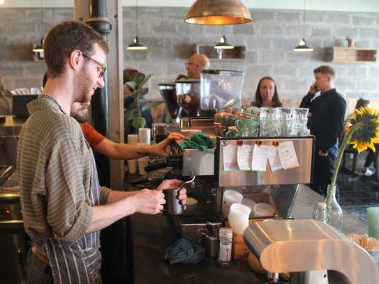 Niall Ford, 21, makes coffee for customers at the Food