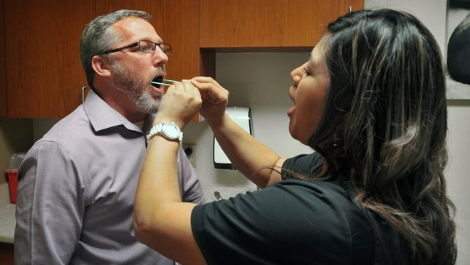 Angela Moreno, LVN swabs the mouth of Wichita Falls Times Record News Business Editor John Ingle  recently at Olney Hamilton Hospital. Ingle experienced first-hand pharmacogenetic testing which uses a patient's DNA to help a doctor determine the most effective drug and dosage for each individual.