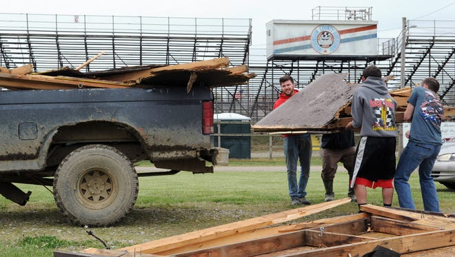 Brian Hartum and brothers Brodie, Wylie and Devin Moran, all of Dresden, tear down and load up what is left of an old ticket booth in preparation for opening night at the Muskingum County Speedway.