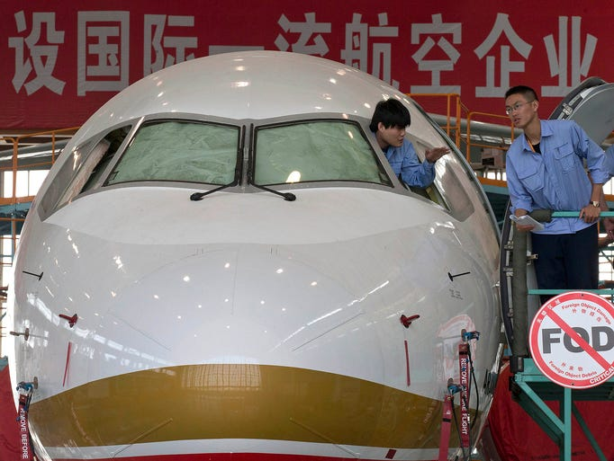 A worker peers from the cockpit of an almost completed Comac ARJ21-700 passenger jet at a final assembly and manufacturing center on May 21 in Shanghai. The state-owned aircraft maker Comac is ready to deliver China's first homegrown regional airliner.