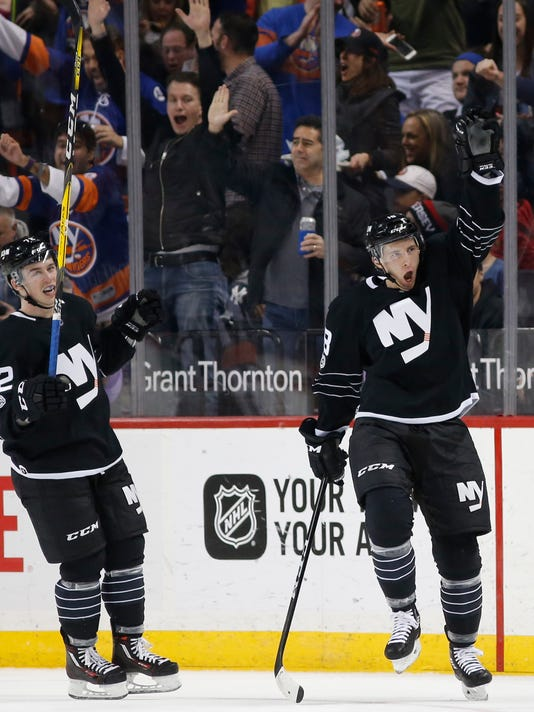 New York Islanders right wing Ryan Strome (18) reacts after scoring a goal during the first period of an NHL hockey game against the New Jersey Devils, Sunday, Feb. 19, 2017, in New York. Islanders left wing Anthony Beauvillier (72) joins in the celebration. (AP Photo/Kathy Willens)