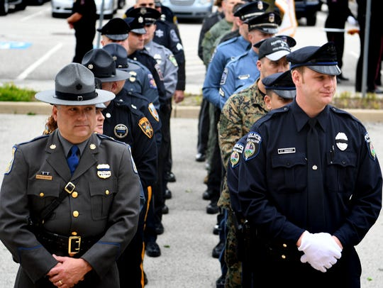 Law enforcement personnel prepare to enter the memorial