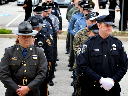 Law enforcement personnel prepare to enter the memorial