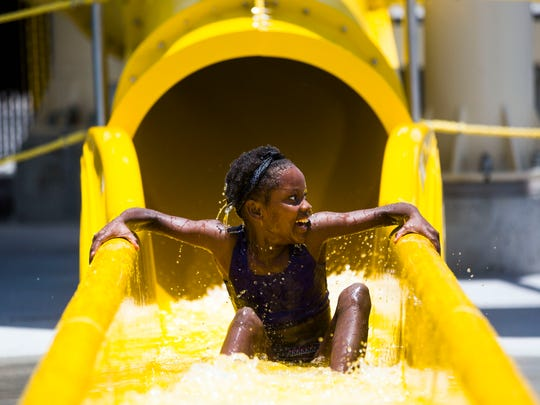 Minoicka, 11, smiles as she slides down one of two