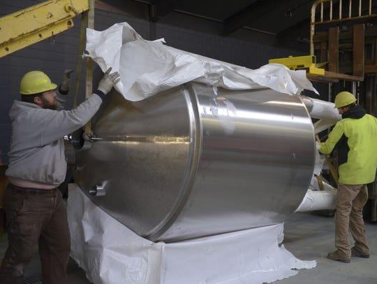 Ben Jerdee of Schuh Construction Inc. unwraps a tank
