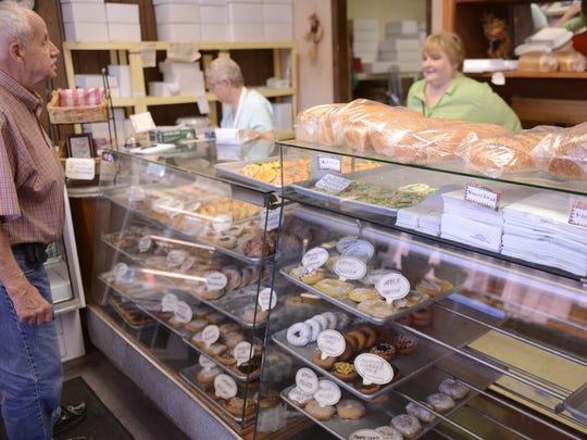 Ed Zenko tells a joke to Jill Baldwin at Willow Street Bakery in Green Bay. Zenko started coming to the east Green Bay bakery in 1969. Willow Street will close after business on Oct. 31.