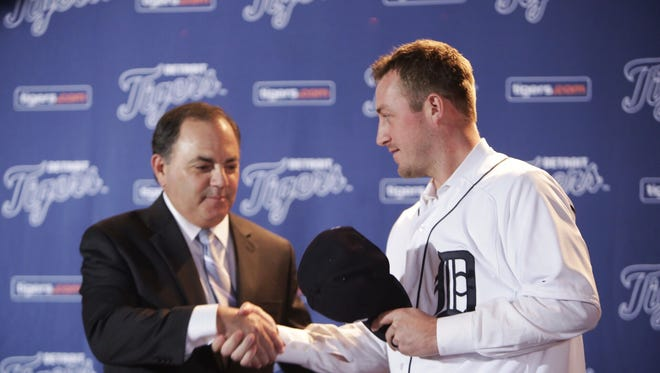 Detroit Tigers GM Al Avila shakes hands with Jordan Zimmermann after putting on his Detroit Tigers jersey after being named their new right-handed pitcher during a press conference November 30, 2015 at Comerica Park in Detroit.