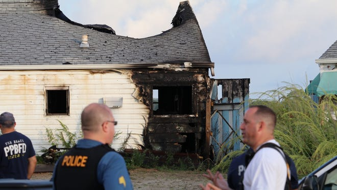 Point Pleasant Beach police and firefighters are shown outside 47 Inlet Drive Sunday, August 21, 2016, after an overnight fire destroyed the structure.