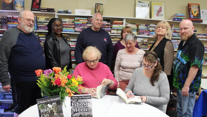 "The Malice in Memphis crew gathered around the table to take turns signing their first two books of the Malice in Memphis book series, ""Bluff City Mysteries,"" and ""Ghost Stories."" Pictured (front, left to right): Editor, Carolyn McSparren, and MIM president, Kristi Bradley; (back, from left) Richard Powell of Germantown, Angelyn Sherrod of Memphis, Jim Paavola of Memphis, Juanita Houston of Munford, Barbara Christopher of Eads, Susan Wooten of Jonesboro, and Larry Hoy of Collierville."
