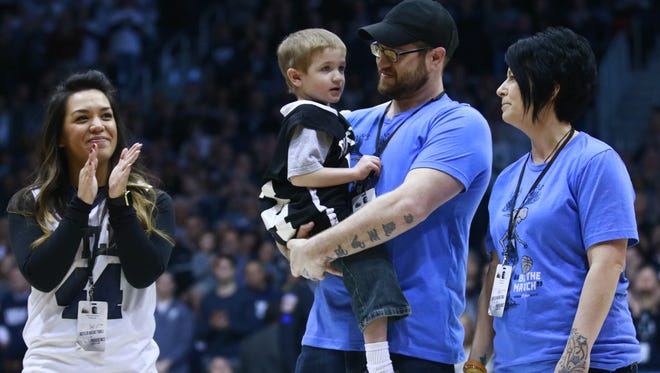 Samantha Smith (left) joins Cliff and Amy Scott, and their son Deegan (middle) at midcourt Saturday at Hinkle Fieldhouse.