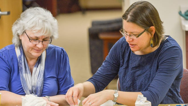 """Healing through Art"" instructor Lynn Genz, right, works with Sandra Halbur on a personal photo collage using Mod Podge to create a photo transfer."