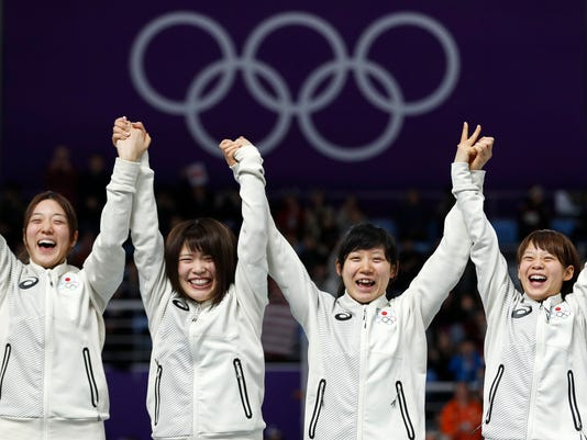 Gold medalist team Japan with Ayaka Kikuchi, Ayano Sato, Miho Takagi, and Nana Takagi, from left to right center, left, celebrates on the podium after after the women's team pursuit final speedskating race at the Gangneung Oval at the 2018 Winter Olympics in Gangneung, South Korea, Wednesday, Feb. 21, 2018. (AP Photo/John Locher)