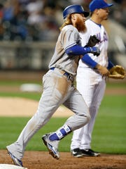 Los Angeles Dodgers Justin Turner rounds first base past New York Mets first baseman Wilmer Flores after hitting a third-inning, two-run, home run off New York Mets starting pitcher Steven Matz in a baseball game, Sunday, Aug. 6, 2017, in New York. (AP Photo/Kathy Willens)